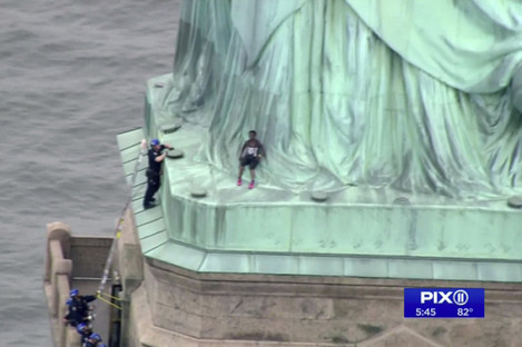 Police officers climbed up on a ladder to stand on a ledge nearby talking the climber into descending in New York