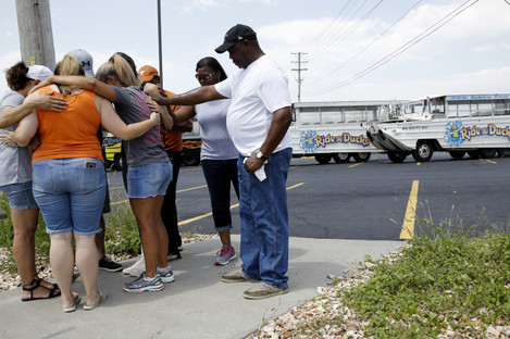 People pray outside Ride the Ducks, an amphibious tour operator involved in last night's duck boat accident
