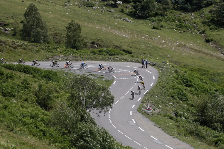 The group of leaders, with Geraint Thomas wearing the overall leader's yellow jersey, speeds down Col du Tourmalet pass.