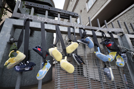 Pairs of baby shoes hang from the railings on Sean McDermott Street in Dublin in memory of the children who died at the mother and baby home in Tuam.