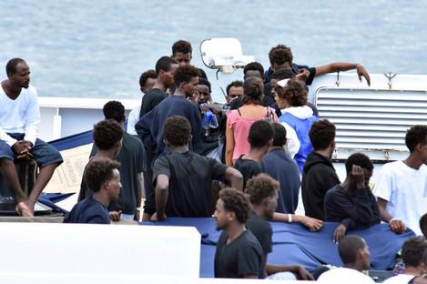 Migrants wait to disembark from Italian Coast Guard ship Diciotti in the port of Catania, Italy.