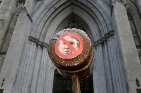 A protester holds a gavel with a picture of Brett Kavanaugh in New York.