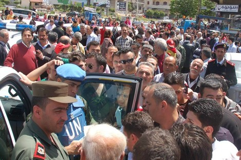 A UN observer and Syrian army officer, left, listen to Syrian citizens during their visit to the pro-Syrian regime neighborhoods, in Homs province yesterday.