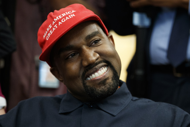 Kanye West smiles as he listens to a question from a reporter during a meeting in the Oval Office of the White House with President Donald Trump