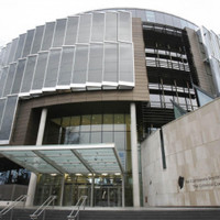 Woman suspected of slicing civil servant's throat goes on trial