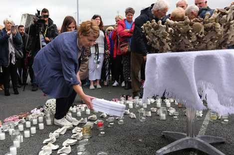 """Historian Catherine Corless places a """"baby's coffin"""" at a temporary shrine to the babies who died in the Tuam mother and baby home."""