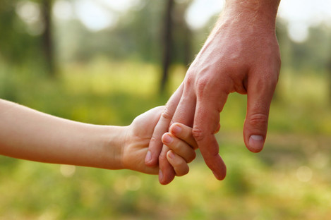 File photo of an adult and child holding hands.