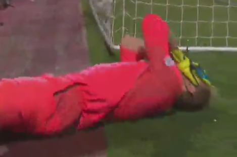 Hearts goalkeeper Zdenek Zlamal lies on the ground holding his face.