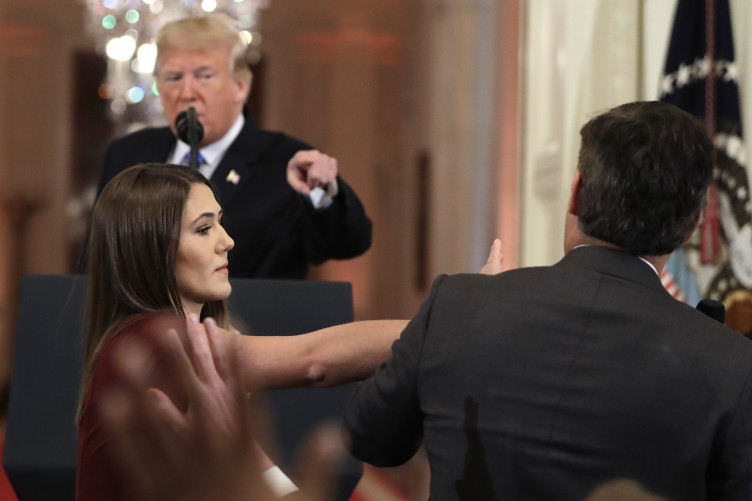 Trump goes on the offensive against reporter Jim Acosta as White House intern attempts to remove his microphone.
