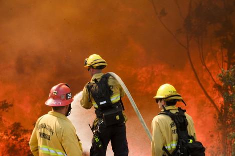 Firefighters battle wildfire near a freeway in Simi Valley, California.