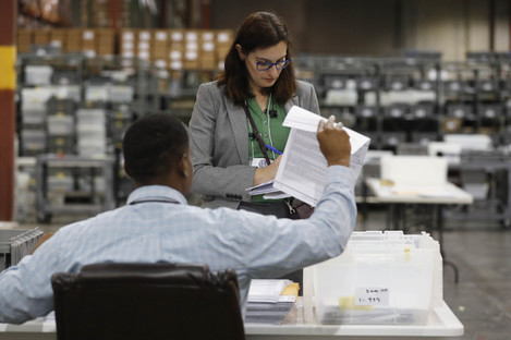 Employees at the Palm Beach County Supervisor of Elections office sort ballot pages during a recount