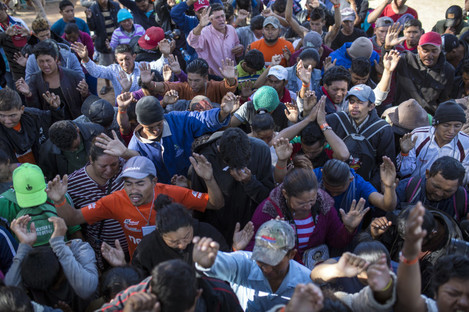 Central American migrants, part of the caravan hoping to reach the US border, pray at a temporary shelter in Tijuana, Mexico