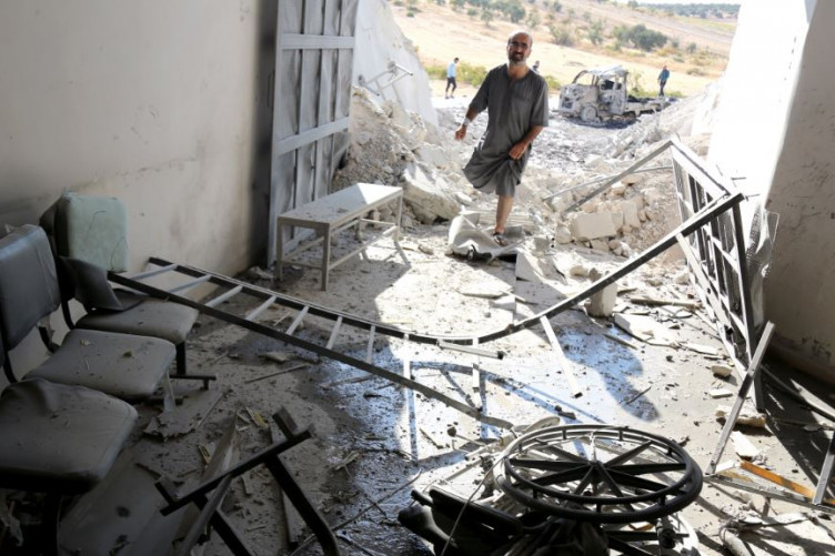 A Syrian man inspects the wreckage at a site after Syrian government airstrikes, which targeted the civilian hospital in Hass, rural Idlib, in September 2018.