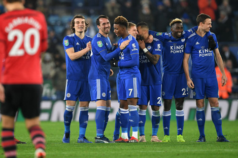 Leicester players celebrates and Southampton's Manolo Gabbiadini walks back after missing a penalty during the Carabao Cup.