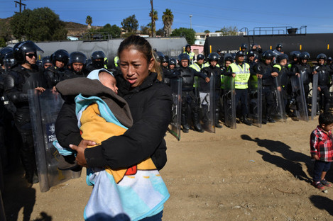 A woman and her 5 month-old baby walk past Mexican police in riot gear moving the migrants away from the border