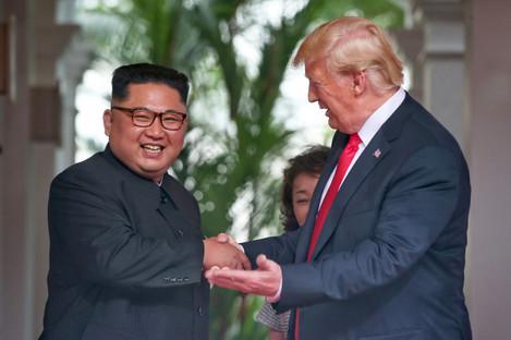 Leader of the Democratic People's Republic of Korea Kim Jong Un (L) with U.S. President Donald Trump in Singapore in June