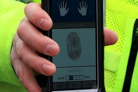 A West Yorkshire Police officer holding a new mobile fingerprint scanning system.