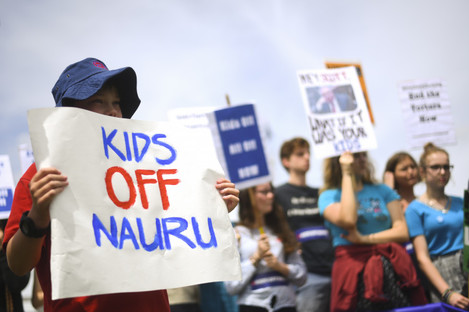 Protesters hold up signs during a rally demanding the resettlement of kids held on Nauru outside Parliament House in Canberra, Australia.