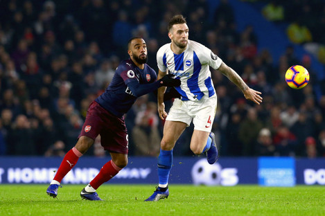 Arsenal's Alexandre Lacazette (left) and Brighton & Hove Albion's Shane Duffy battle for the ball.