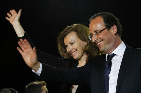 French president-elect Francois Hollande and his companion Valerie Trierweiler wave to supporters after greeting crowds gathered to celebrate his election victory in Bastille Square in Paris, France