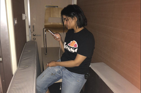 Photo released by Rahaf Mohammed Alqunun/Human Rights Watch, Rahaf Mohammed Alqunan views her mobile phone as she sits barricaded in a hotel room at an international airport in Bangkok, Thailand.
