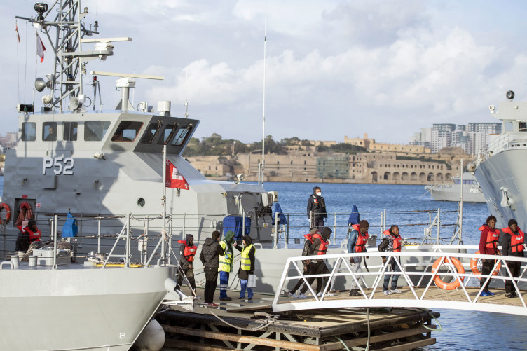 Migrants disembarking from boats that have been given permission to dock in Malta