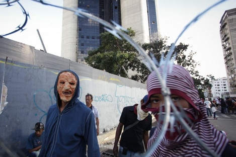 Masked protesters seen behind a fence during a mass protest against Venezuelan President Nicolás Maduro in Caracas this week.