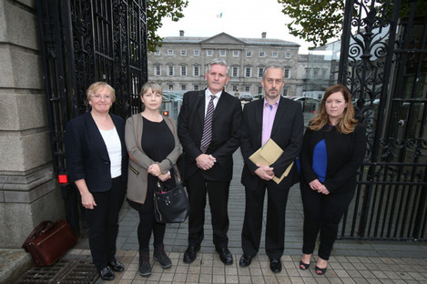 A group of tracker mortgage scandal victims, with financial adviser Padraic Kissane (centre) after a hearing in Leinster House.