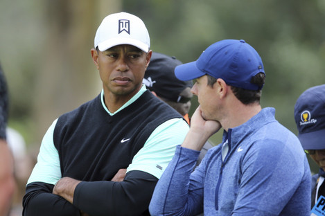 Tiger Woods and Rory McIlroy talk on the 10th green on Friday.
