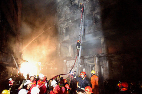 Rescuers work at the fire site in Dhaka