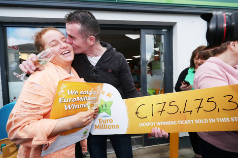 Les Reilly kisses his niece Carly Reilly outside Reilly's Daybreak in Naul, Co Dublin, as they celebrate selling the EuroMillions €175 million winning lotto ticket.
