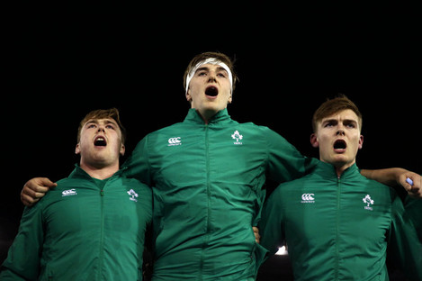Head and shoulders above: Ryan sings the anthems before the clash with Italy.