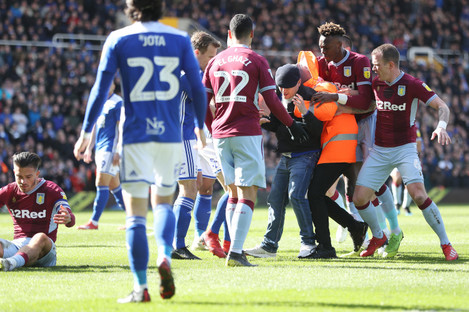 A fan is held is held after attacking Aston Villa's Jack Grealish (left).