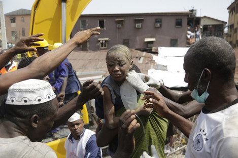 A child is rescued from the rubble of a collapsed building in Lagos, Nigeria