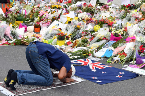 A muslim worshipper prays at a makeshift memorial at the Al Noor Mosque on Deans Rd in Christchurch, New Zealand