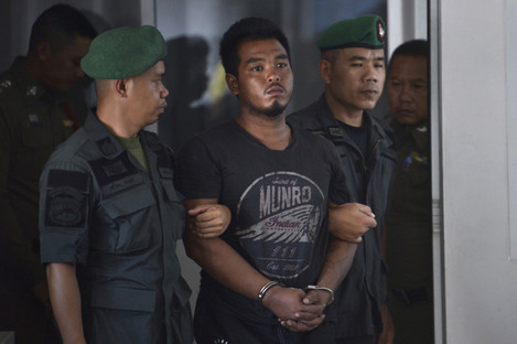 Ronakorn Romruen is escorted by police as he arrives at Koh Sichang police station