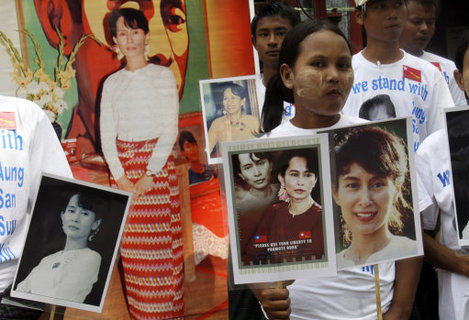 Members of Suu Kyi's National League for Democracy (NLD) hold her portraits as they gather at the party's headquarters today.
