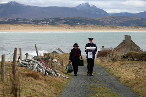 Presiding Officer Carmel McBride and Garda Sergeant Paul McGee carry a ballot box away from a polling station after voting concluded on the island of Inishbofin in 2016.
