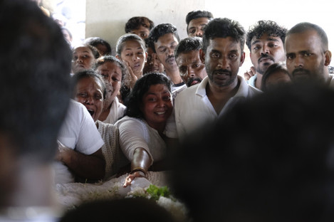 Relatives of a victim of the explosions mourn during a funeral in Colombo.
