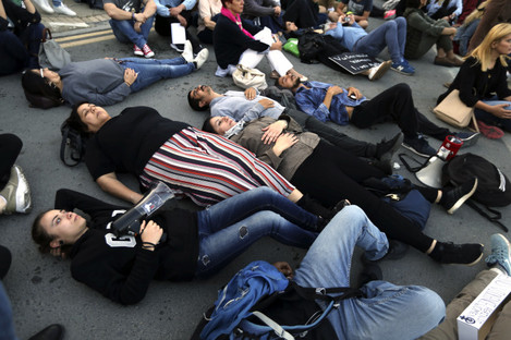 People lie on the street during a protest outside of the presidential palace in Nicosia.