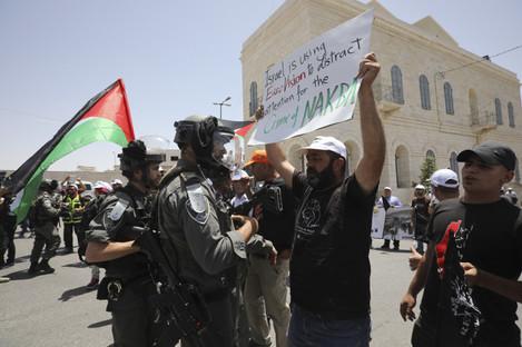 A man holding anti-Eurovision banner confronts an Israeli border policeman
