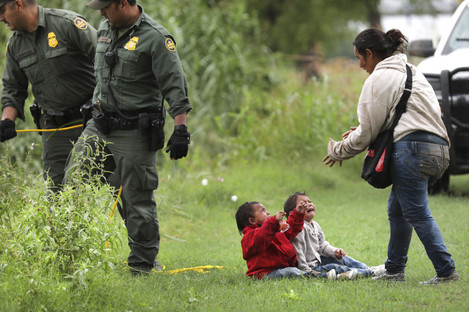 A mother from Honduras goes to her two children after Border Patrol agents react to makeshift rafts crossing the Rio Grande River near Eagle Pass, Texas.