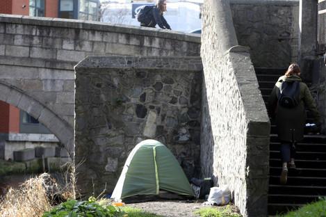 A woman walks past a homeless tent iunder a bridge in Dublin earlier this year.