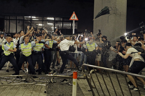 Police officers use pepper spray against protesters