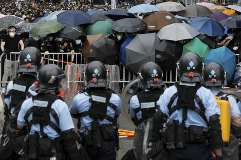 Policemen in anti-riot gear stand watch as protesters use umbrellas to shield themselves.