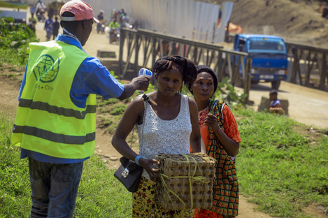 People crossing the Uganda-Congo border have their temperature checked for symptoms.