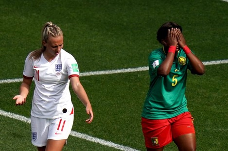 England's Toni Duggan (left) reacts after she is spat on by by Cameroon's Augustine Ejangue (right).