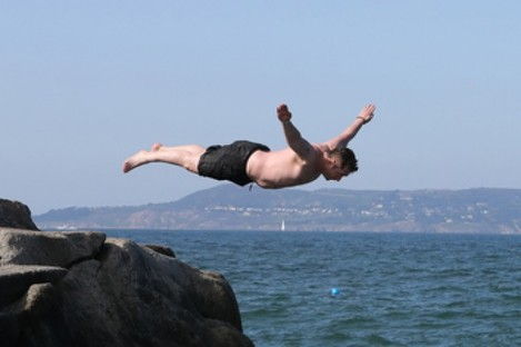 A man dives into the Forty Foot in Sandycove, Dublin.