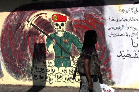 """An woman passes by a wall with graffiti depicting the ruling military council and Arabic that reads, """"you sold my blood cheap, you supported the killer but not me, I am the martyr,"""" in Cairo."""