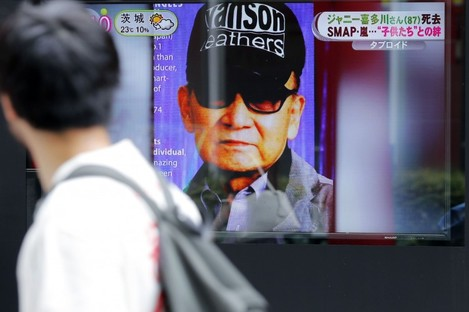 A passer-by watches a TV news reporting Johnny Kitagawa's death